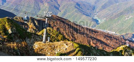 Mountain zipline through autumn forest on backdrop of Caucasus mountains funicular railway to observation deck tops 2320 m. Krasnaya Polyana - Alpine ski resort constructed from 2003 to 2011 for Sochi games. Rosa Khutor Sochi Russia