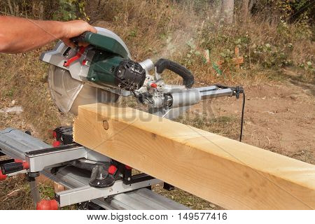 Construction Worker Cutting Beam with saw. Workers cutting timber wood with chainsaw. Saw sawing timber.