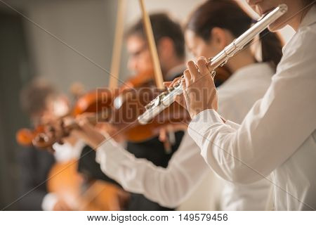 Professional female flustist playing her instrument on stage with classical music symphony orchestra unrecognizable person
