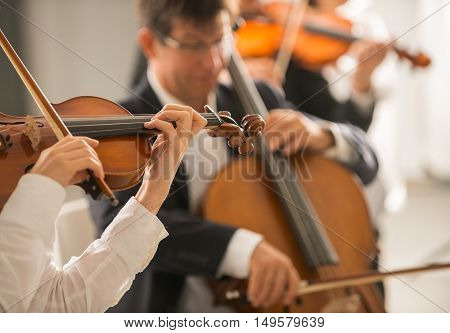 Female violinist performing and classical orchestra on background selective focus music and arts concept
