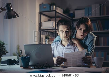Young Couple Checking Bills At Night