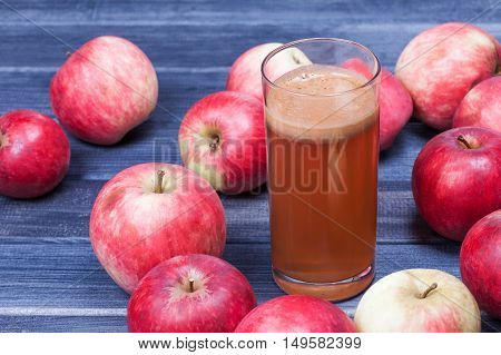 Fresh Apple juice and apples on wooden table