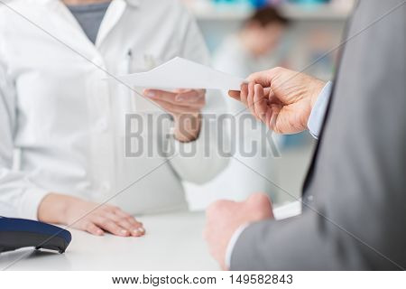 Male customer at the pharmacy he is giving a prescription to the pharmacist hands close up