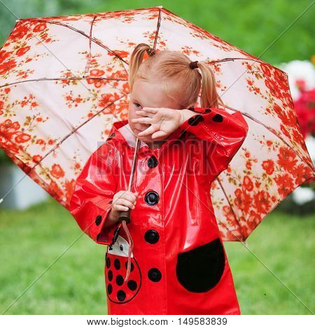 Sad Pretty Little Girl In Red Raincoat With Umbrella Walking In Park Summer