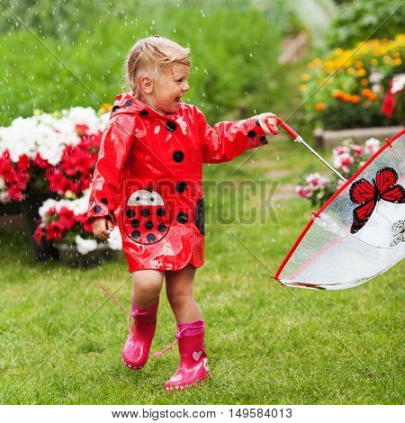 Happy Fun Pretty Little Girl In Red Raincoat With Umbrella Walking In Park Summer