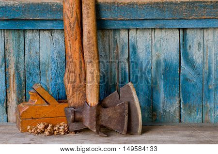Old ax pickaxe wooden plane and chips on a background of the old wall