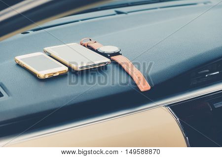 Closeup of watch and mobile phone lying inside car against photography retro.