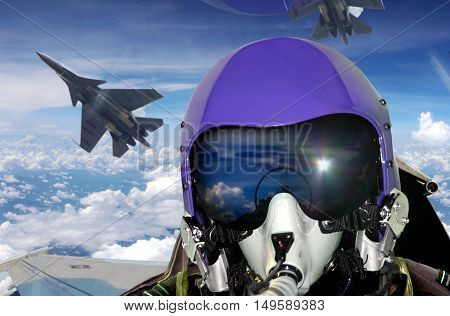 Jet fighter pilot cockpit view under clear sky