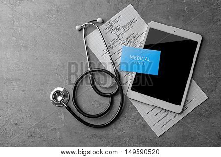 Medical service concept. Visiting card, cardiogram, stethoscope and tablet on grey background