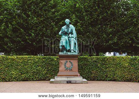 Copenhagen, Denmark - September, 22th, 2015. Hans Christian Andersen statue in Rosenborg garden. Bronze sculpture of famous danish fairy tale writer amid green plants.