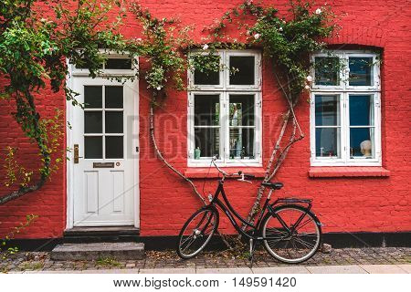 September, 23th, 2015 - Copenhagen, Denmark. Street, wall and bike. White color windows, door and modern bicycle leaned to red wall with blossom flowers.