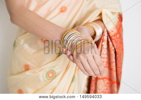Fair skin Indian woman in traditional sari dress wearing bangles, standing on plain background.