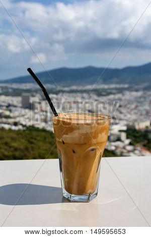 Ice frappe coffee and view of town of Athens for background