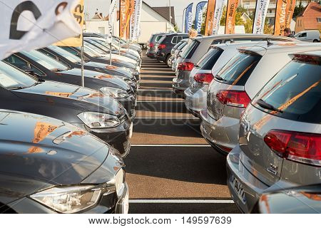 PARIS FRANCE - OCT 10 2015: Mature woman walking between rows of new car to choose the most precious one at the Volkswagen and BMW store car automotive