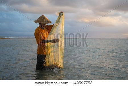 Bali, Indonesia, September, 2016: old fisherman in a sea in Bali Indonesia