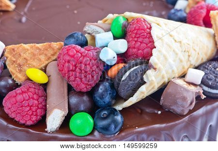Ice cream cone filled with berries and sweets