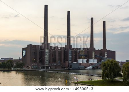 WOLFSBURG GERMANY - SEP 23 2016: View of the old Volkswagen factory building with the illuminated VW logo