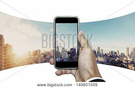 Businessman hand taking panoramic photo of Bangkok cityscape in sunrise
