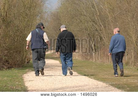 Three Men Walking Together On Country Track