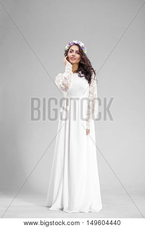 Young arabic woman in white sexy dress, isolated on gray background