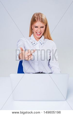 Young businesswoman working at laptop computer. hiding behind the monitor. frustrated, spiteful woman in shock showing middle finger
