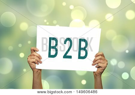 B2B (marketing) card in hand with abstract light background. Selective focus.