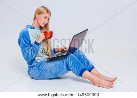 girl in pajamas with a laptop lying on the floor. studying or doing online shopping. work from home. Satisfied and smiling. drinking coffee or tea