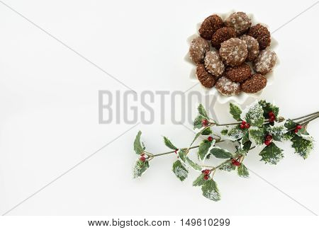Homemade authentic German Gingerbread cookies and an artificial Holly Berry Branch as Christmas decoration. Lots of copy space.