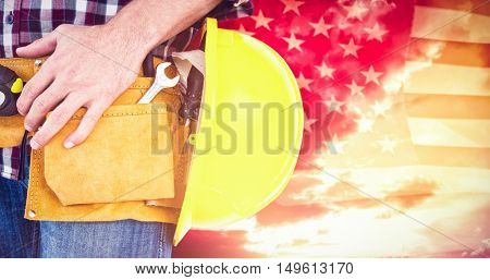 Handyman with tool belt and handyman against american flag rippling over grassy landscape