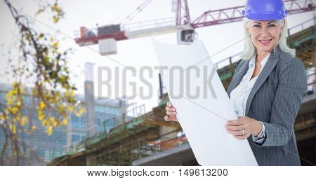 Selfassured businesswoman wearing a helmet against crane and building construction site Crane and building construction site on a sunny day
