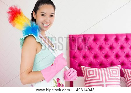 Smiling woman with duster against pink bed headboard