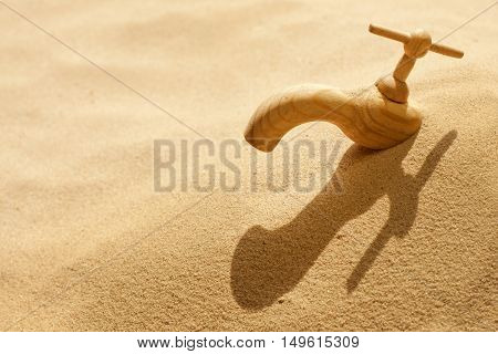 Global warming climate change faucet in the sand concept