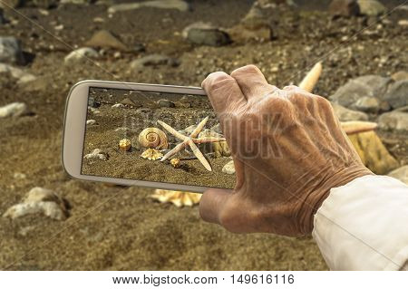 Old hand takes a picture of starfish and sea shells on smart phone. Selective focus.