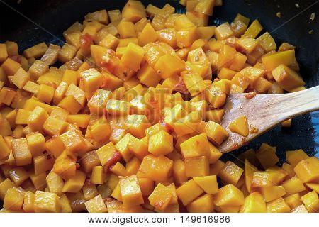 Stir fried sliced pumpkin vegetables in a pan. Cooking process.