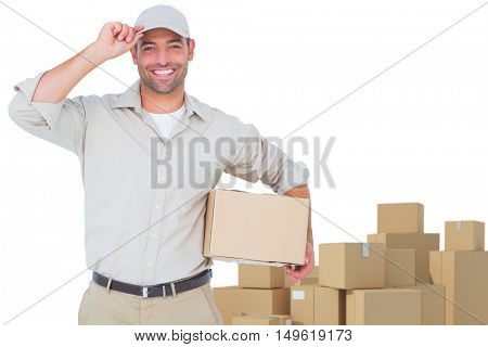 Portrait of happy delivery man with cardboard box wearing cap against arrangements of cardboard boxes