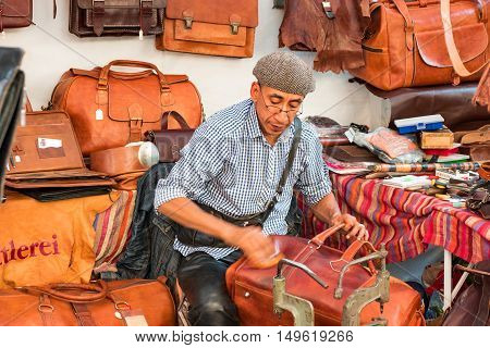 Leather manufacturing: craftsman / leather-dresser surrounded by leather goods at work polishing very quickly  a new leather bag - September 24 2016, fall market, Heidelberg, Germany