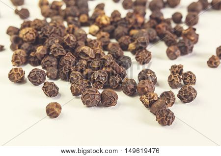 Black pepper isolated on light background. Selective focus.