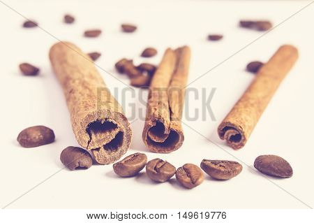 Close up of cinnamon sticks and coffee beans in blurred background.