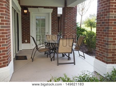 a table and four chairs on a covered patio by a brick building.
