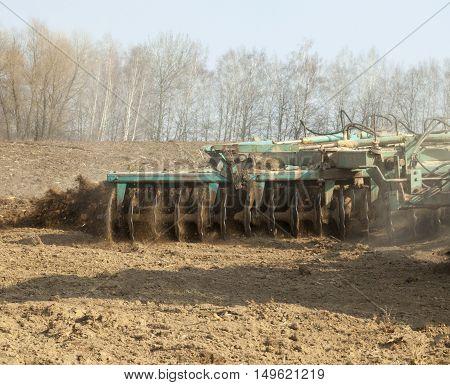 Harrowing the soil with disc harrows in spring in Ukraine.
