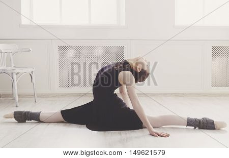 Classical Ballet dancer portrait. Beautiful graceful ballerine in black practice split ballet position in class room background. Ballet class training, high-key soft toning. Vertical image