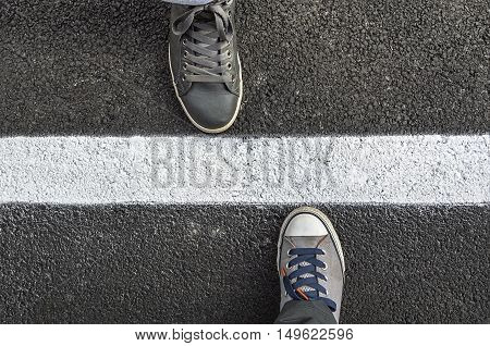 Top view of sneakers from above standing next to white street lines. Selective focus