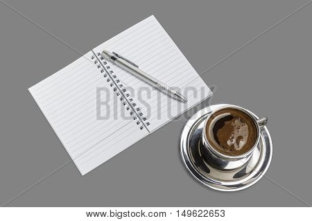 Coffee cup with open blank notebook and pencil isolated on gray background.