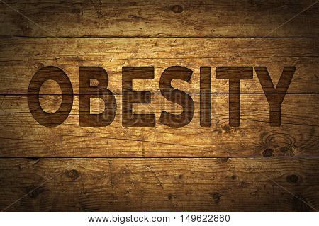 Word Obesity written on wooden background. Vintage and vignette effect applied