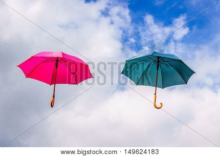 Red Umbrella and Green Umbrella floating in the Air under Blue Sky and Clouds