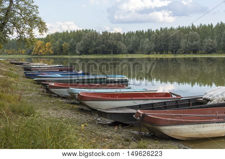 A group of boats on the beach by the lake in the autumn. Selective focus.
