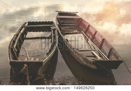 Old flooded wooden boats on river. Selective focus.