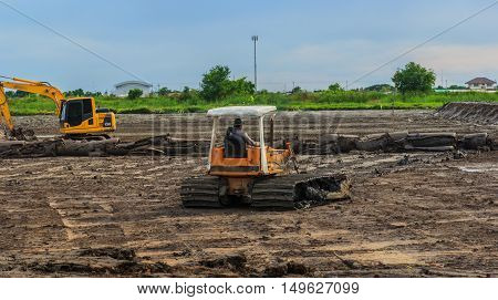 An car dozer working removing earth on a construction site.