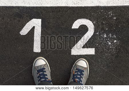 Feet concept with sneakers on asphalt road with 1 and 2 number