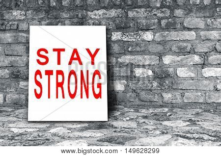 Stay strong sign on floor in black interior